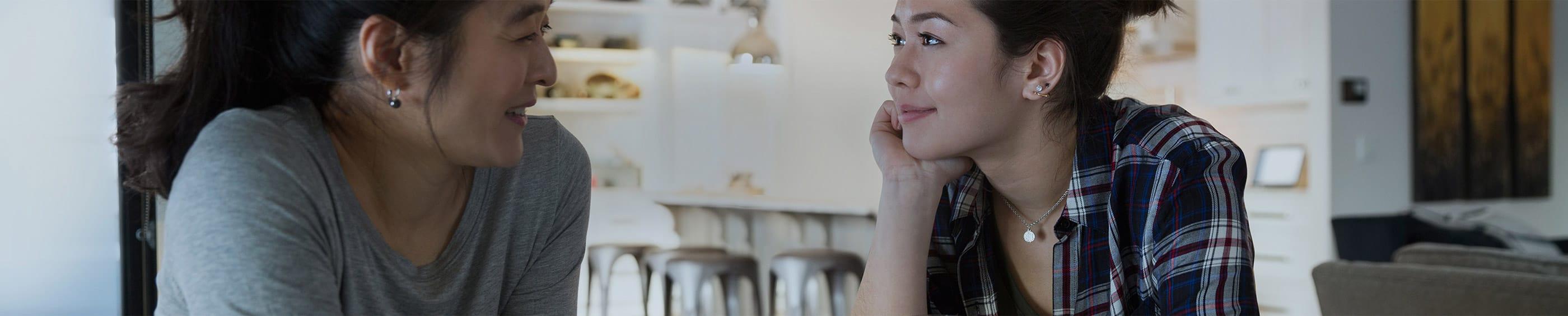 Una joven mujer hablando con su madre en la cocina